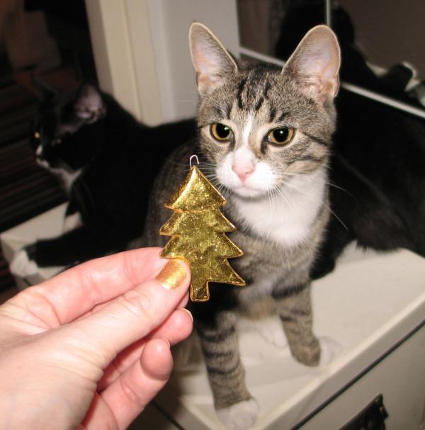 Z tuijottaa kultaista joulukuusen muotoista koristetta, Ilona murjottaa taustalla