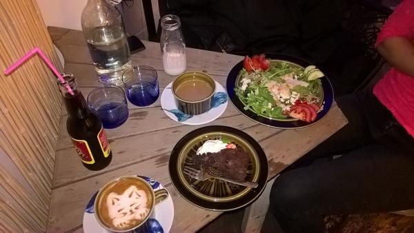 meiän pöydässä on pari kahvia, salaattia, kakkua, vettä, limsaa