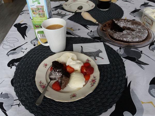 kahvia. lautasella mansikoita, jätskii ja mutakakkua.