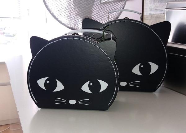 kaksi samanlaista laukkua, mutta eri kokoisia. Kissan naama, musta. Valkoisella silmät ja viikset. Ja korvat on kans.
