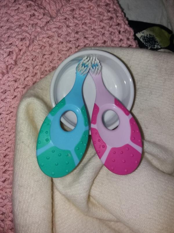 pinkki ja vaaleansininen vauvaharja, kummassakin tukeva lenkurapää jota vauva voi joutessaan pureskella