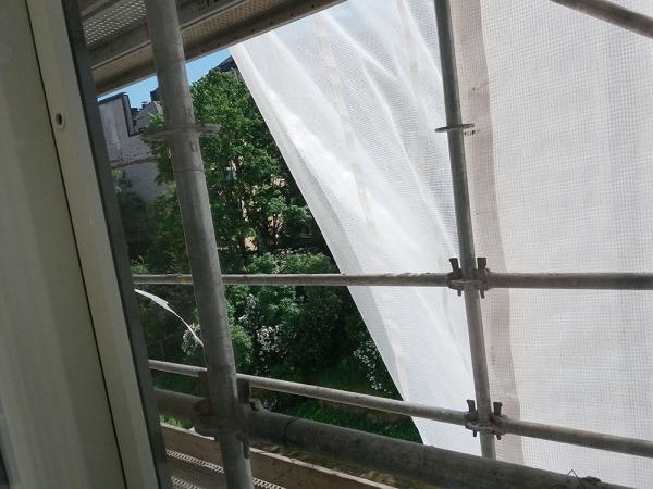 raksan valkoinen suojamuovi repeää tuulen mukana nätisti ja palauttaa meille näkymän koivuihin ja syreenipensaisiin