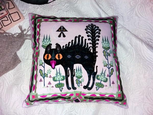 klaus haapaniemen kissatyyny, musta tyylitelty kissa sähisee turkki ja häntä pörhössä